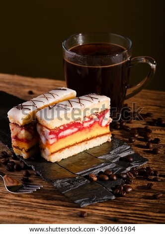 Vertical photo of two slices of sweet desert with color layers on sugar on the top placed on piece of black stone. Cup of coffee is in background on wooden board with few coffee grains around. - stock photo