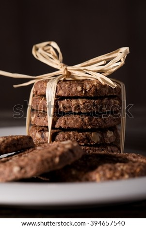 Vertical photo of white plate placed on wooden board with few brown cereal biscuits. Few biscuits are placed in a stack bonded by yellow straw.  - stock photo
