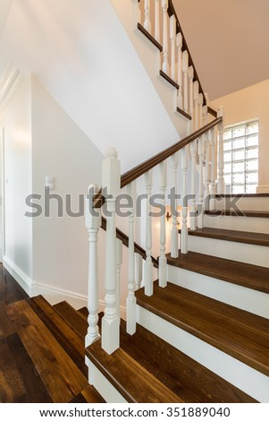 Vertical photo of wooden stairs in a luxurious storey house - stock photo
