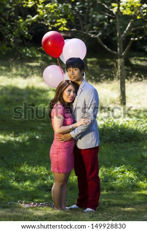 Vertical photo of young adult couple dressed in formal attire holding each other outdoors with several balloons and trees behind them   - stock photo