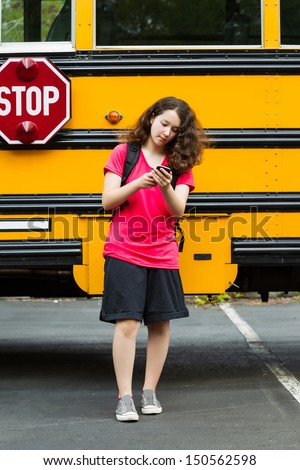 Vertical photo of young girl walking away from school bus, with back pack over her shoulders, while on her phone - stock photo