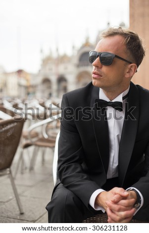 Vertical photo of young handsome man in tuxedo sitting in outdoor cafe - stock photo
