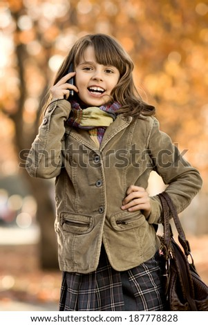 vertical photo,  stylish beautiful little girl hold  mobile phone and gladness talk - stock photo
