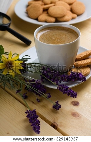Vertical photo with cup of coffee on square saucer with few biscuits. Other biscuits are on plate in background. Lavender and sunflowers are next to cup. All is on wooden board.