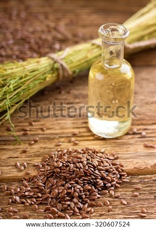 Vertical photo with heap of flax seeds spilled on old worn wooden board with glass bottle full of flax oil and with bunch of flax plants bonded by natural cord. - stock photo