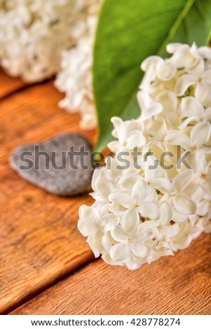 Vertical photo with several flowers of lilac. Single green leaf on lilac blooms. White lilac blooms. Flowers with heart shaped stone placed on wooden board. Grey stone next to flowers. - stock photo