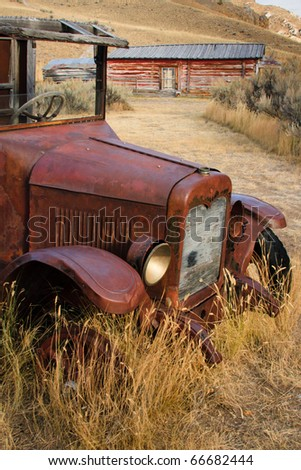 Vertical photograph of an old rusted truck sitting in dry field of grass near a Montana ghost town.