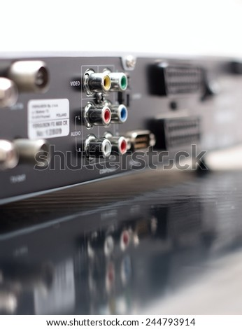 Vertical Picture of rear side of music and video player with focus on color audio connectors in two rows and with visible reflection in the surface of bottom board - stock photo