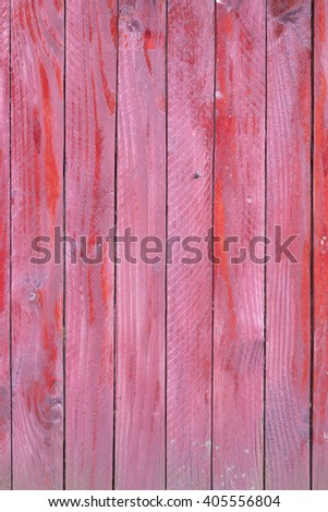 vertical planks of faded red painted worn planks on fence or door - stock photo