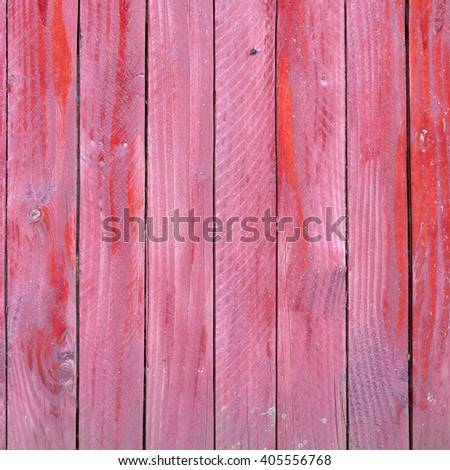 vertical planks of faded red painted worn planks on square piece of fence or door - stock photo