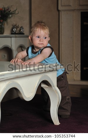 Vertical portrait of a baby boy standing on the floor leaning against a coffee table looking sideways - stock photo