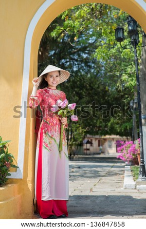 Vertical portrait of a beautiful young lady with lotus bouquet outside