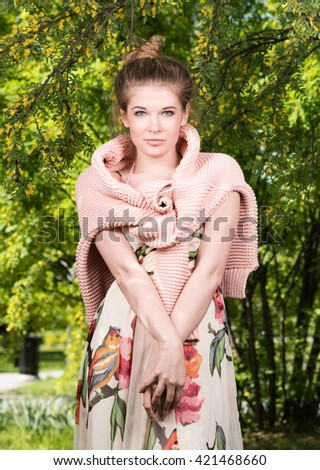 Vertical portrait of a beautiful young woman with a pink sweater on his shoulders in a lush garden. Collected hair, light makeup - stock photo