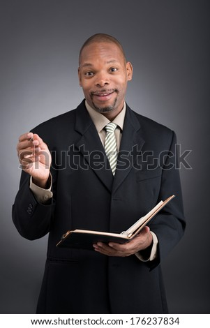 Vertical portrait of a black African businessman with a notepad over grey