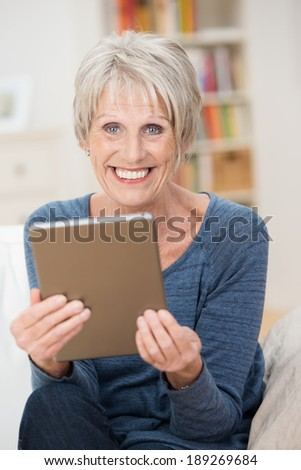 Vertical portrait of a blond Caucasian modern senior woman smiling cheerfully and wearing a casual blue long-sleeve T-shirt while sitting in the living holding a tablet PC