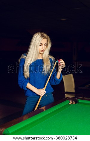 Vertical portrait of a charming blonde rubbed cue chalk. Billiard sport concept. Pool billiard game. American pool billiard. - stock photo