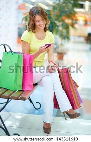 Vertical portrait of a charming girl sitting on a bench in a shopping gallery and reading sms - stock photo