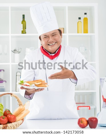 Vertical portrait of a cheerful chef cook showing his dish - stock photo