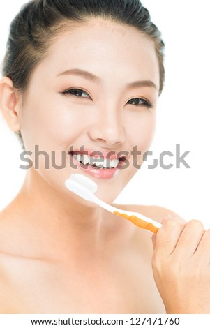 Vertical portrait of a cheerful young woman holding a toothbrush with toothpaste - stock photo