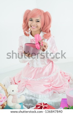 Vertical portrait of a cute princess in pink opening a gift-box