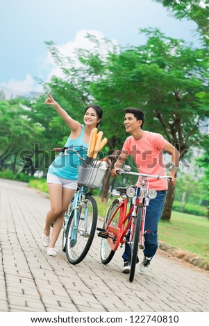 Vertical portrait of a cycling couple after shopping - stock photo