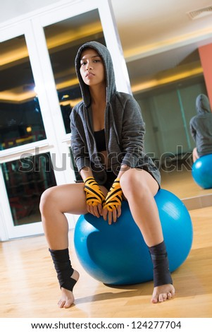 Vertical portrait of a female boxer in hoodie sitting on a gym ball - stock photo