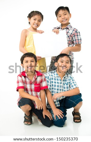 Vertical portrait of a group of little friends holding a promotional banner - stock photo