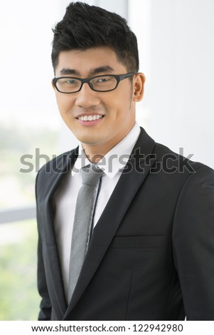 Vertical portrait of a handsome young entrepreneur dressed with elegance