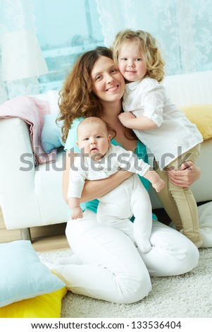 Vertical portrait of a happy family of three looking at the camera - stock photo