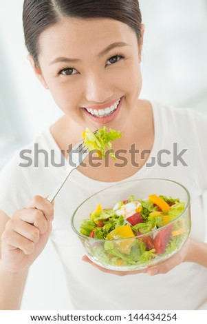 Vertical portrait of a lovely young woman eating healthy - stock photo