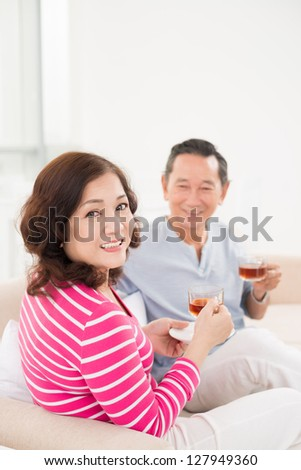 Vertical portrait of a senior couple drinking tea at home - stock photo