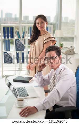 Vertical portrait of a serious businessman at his workplace while his secretary standing on the foreground
