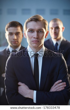 Vertical portrait of a serious leader of the company standing on the foreground  - stock photo