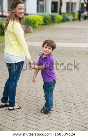 Vertical portrait of a smiley mother and her son standing in the street  - stock photo
