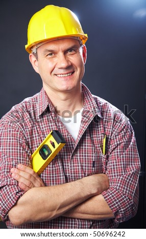vertical portrait of a smiling handsome man-builder on a dark background - stock photo