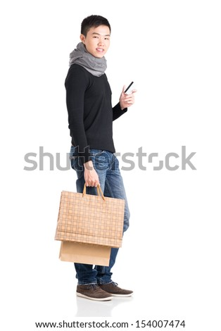 Vertical portrait of a stylish young man standing with a credit card and shopping bags over a white background - stock photo