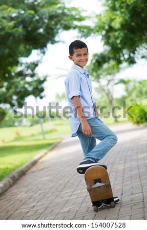 Vertical portrait of a young guy with a skate in the park - stock photo