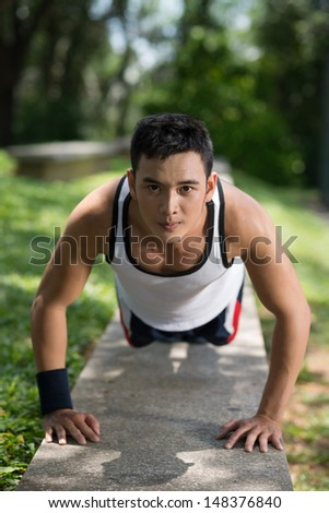 Vertical portrait of a young sporty man doing push-ups outside