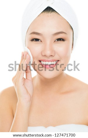 Vertical portrait of a young woman cleansing her face with a cotton pad - stock photo