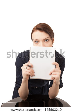 Vertical portrait of a young woman holding a notebook and a pen, standing, on white background