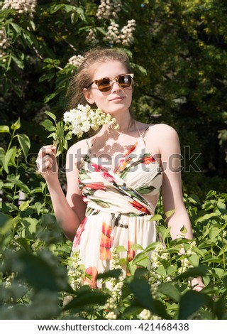Vertical portrait of a young woman in sunglasses and dress in the park. Flowering trees in the background