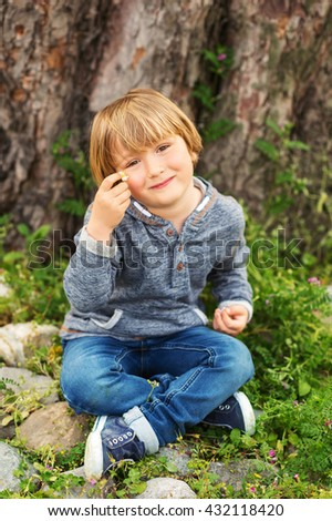 Vertical portrait of adorable little boy of 4-5 years old, wearing blue hoody, playing alone outdoors - stock photo