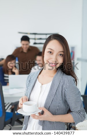 Vertical portrait of an attractive smiling businesswoman on the foreground