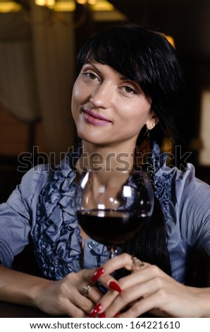Vertical portrait of an elegant brunette young woman smiling while drinking a glass of red wine at the bar - stock photo