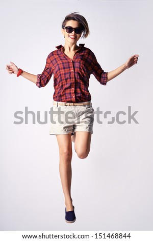 Vertical portrait of an energetic young woman making a perfect pose when jumping - stock photo