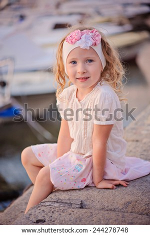 vertical portrait of beautiful smiling child girl in pink outfit sitting on sea side in summer day with boats on background - stock photo