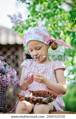 vertical portrait of cute 5 years old girl in pink plaid dress making lilac wreath in spring garden