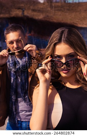 Vertical portrait of fashionable couple in sunglasses both outdoors - stock photo