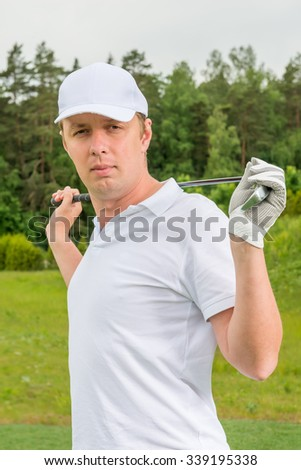 Vertical portrait of golfer with golf club - stock photo