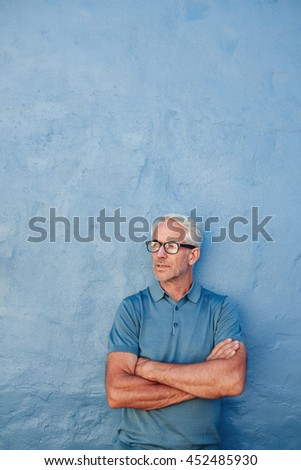 Vertical portrait of handsome mature man standing with his arms crossed and looking away against blue background. - stock photo